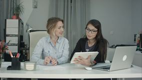 Glimlachend commercieel vrouwelijk team die met tabletpc werken in het bureau royalty-vrije stock fotografie