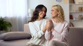Glimlachend de homoseksuele vrouwelijke handen van de paarholding op gelukkige bank thuis, samen royalty-vrije stock afbeeldingen