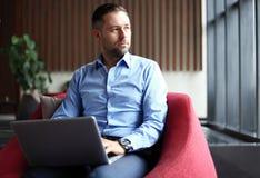 Glimlachend de jonge knappe kop van de zakenmanholding van koffie en binnen werkend met laptop in koffie Royalty-vrije Stock Fotografie