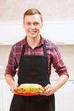 glimlachend de plaat van de mensenholding met grote sandwich Stock Afbeeldingen