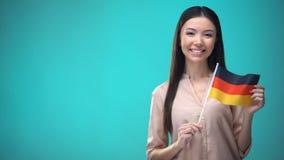 Glimlachend de vlag van Duitsland van de dameholding klaar om vreemde taal, Duitse school te leren stock footage