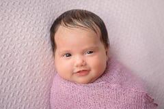 Glimlachend die Babymeisje in een Lavendelomslag wordt ingewikkeld royalty-vrije stock fotografie