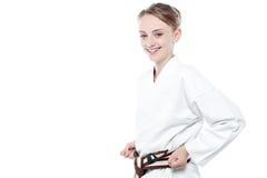 Glimlachend die karatemeisje over wit wordt geïsoleerd Stock Foto's