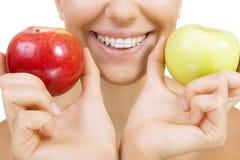 Glimlachend die meisje met pal voor tanden en appel, op whit wordt geïsoleerd stock foto's