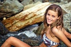Glimlachend donkerbruin meisje op rots in een rivier Stock Afbeeldingen
