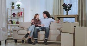Glimlachend en charismatisch jong paar die van de tijd in genieten een nieuw huis, met dozen rond na een bewegende dag zij stock footage
