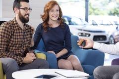Glimlachend en gelukkig huwelijk die een nieuwe auto in exclusieve showroo kopen stock foto's