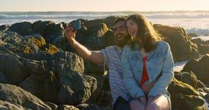 Glimlachend gelukkig jong paar die selfie op rots bij het strand 4k klikken stock video