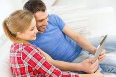Glimlachend gelukkig paar met tabletpc thuis Stock Afbeeldingen