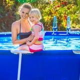 Glimlachend gezond moeder en kind in swimwear in zwembad stock afbeeldingen