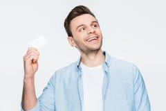 Glimlachend in hand de creditcard van de mensenholding en weg kijkend op wit Stock Fotografie