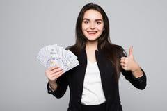 Glimlachend het geld van de bedrijfsvrouwenholding met duimen omhoog over grijze achtergrond royalty-vrije stock foto