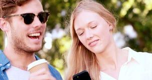 Glimlachend heuppaar die smartphone gebruiken stock videobeelden