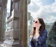Glimlachend hipster meisje die in koele vrijetijdskleding op mobiele telefoon spreken, die zich in openlucht op de straat bevinde royalty-vrije stock afbeeldingen