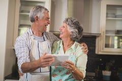 Glimlachend hoger paar die digitale tablet houden terwijl status in keuken royalty-vrije stock fotografie