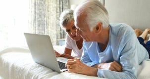 Glimlachend hoger paar die laptop op bed in slaapkamer met behulp van stock video