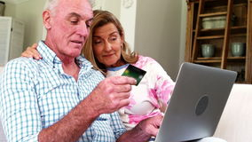 Glimlachend hoger paar die online het winkelen op laptop in woonkamer doen