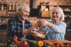 Glimlachend hoger paar die salade samen in keuken maken royalty-vrije stock afbeeldingen