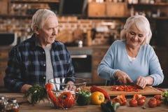 Glimlachend hoger paar die salade samen in keuken maken stock afbeelding