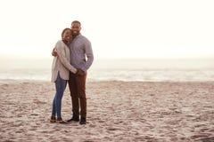 Glimlachend jong Afrikaans paar die zich op een strand bij zonsondergang bevinden stock fotografie