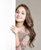 Glimlachend jong donkerbruin meisje met leeg wit teken. royalty-vrije stock afbeelding