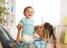 Glimlachend jong geitje en mamma die een prettijdverdrijf op vloer in kinderenruimte thuis hebben stock foto's