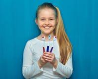 Glimlachend jong geitjemeisje die toothy borstel drie houden Portret op blauw royalty-vrije stock afbeelding