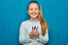 Glimlachend jong geitjemeisje die toothy borstel drie houden Portret op blauw royalty-vrije stock fotografie