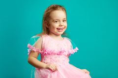 Glimlachend jong geitjemeisje in roze kleding op geïsoleerd blauw stock afbeelding
