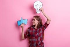 Glimlachend jong meisje die een beeld van een bol en een duim-omhooggaand teken houden en het bekijken Concept het idee stock foto's