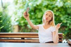 Glimlachend jong meisje die selfie foto op smartphone maken stock fotografie