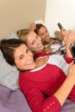 Glimlachend jong meisje drie die op bed liggen Stock Fotografie