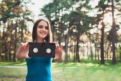 Glimlachend Jong Meisje met een cassette in haar handen stock foto