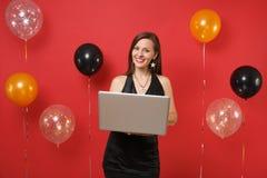 Glimlachend jong meisje in weinig zwarte kleding die aan laptop de computer werken van PC terwijl het vieren op rode achtergrondl stock foto