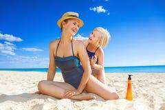 Glimlachend jong moeder en kind die op kust SPF toepassen royalty-vrije stock fotografie