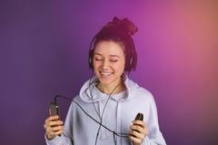 Glimlachend jong mooi meisje die met witte tanden aan muziek op de telefoon luisteren die hoofdtelefoons in een sweatshirt op a d royalty-vrije stock foto's