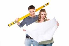 Glimlachend jong paar die met niveauhulpmiddel blauwdruk bekijken Stock Fotografie