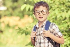 Glimlachend jong schoolkind in een school eenvormig tegen een boom binnen Stock Afbeelding