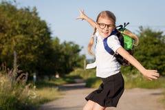 Glimlachend jong schoolmeisje in school het eenvormige springen op roa Stock Afbeeldingen