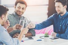 Glimlachend jong zakenlieden drinkwater en het bespreken van nieuwe projectzaken stock foto's