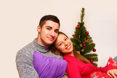 Glimlachend jongen en meisje met hoofdkussens en een Kerstboom   Royalty-vrije Stock Afbeelding