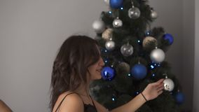 Glimlachend Kaukasisch jong paar die de spar thuis met buitensporige blauwe en zilveren gekleurde ballen verfraaien Samen vul stock footage