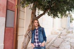 Glimlachend Kaukasisch meisje Een meisje met lang haar in een denimkostuum leunde haar ellebogen op de olijfboom stock afbeelding