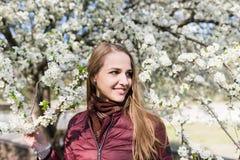 Glimlachend Kaukasisch meisje met lang bruin haar in de bloeiende tuin Het meisje is gekleed in een kleur van jasjemarsala Stock Fotografie