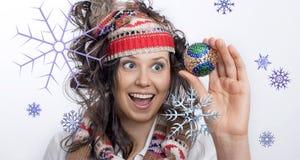 Glimlachend Kerstmismeisje en een hand met Kerstmisstuk speelgoed Stock Fotografie