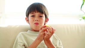 Glimlachend kind die een rode appel eten stock footage