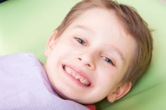 Glimlachend kind met gelukkig gezicht op tandartsstoel of bureau Stock Afbeelding