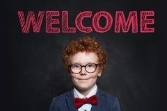 Glimlachend kind met het portret van het gemberhaar Leuk weinig jongen in blauw kostuum tegen bord met welkome inschrijving royalty-vrije stock foto's