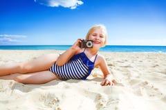Glimlachend kind op zeekust die foto met digitale camera nemen stock fotografie