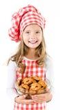 Glimlachend leuk meisje in de holdingskom van de chef-kokhoed met koekjes Royalty-vrije Stock Foto's